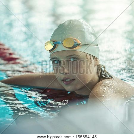 Swimmer child. Portrait of swimming child athlete with glasses after training in waterpool.