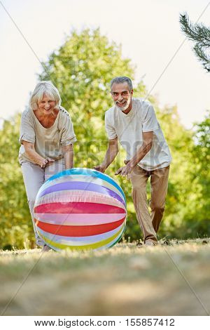 Vitale senior citizens playing with a big bag and having fun in summer