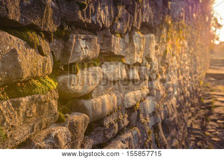 Old Rock Wall. Wild Grasses Growing Out Of Crevices And Cracks Over Old Rock Wall. Ancient Walls Of