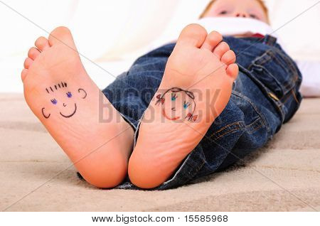 Small faces painted on the soles of a young boy
