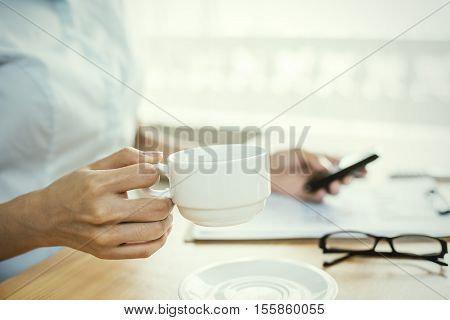 businesswoman drinking coffee and making a phone call