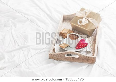 Romantic breakfast with coffee cookies gift box and red plush heart valentines day concept soft vintage tone copy space
