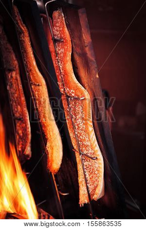 Fish salmon cooking or grilling outside with fire and wood salt and pepper. Cooking or outdoors street food concept