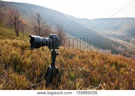 Modern Professional Dslr Camera On A Tripod, Outdoor Photography In Wildlife. Mountains Background.