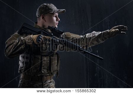 Airsoft - a game for real men. Airsoft is played only real men. Young soldier holding a weapon in the ammunition