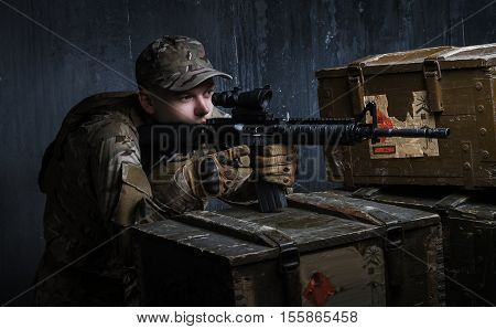 Technology shooting. Coaching in-dash. Man in military uniform with assault rifle aiming at target on background of dark wall
