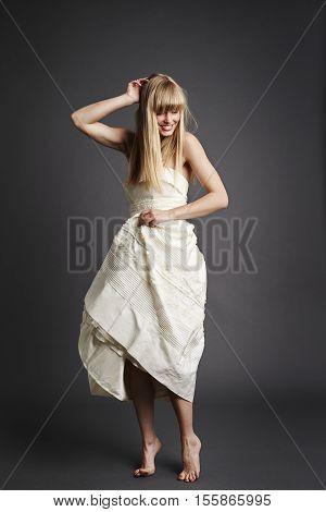 Beautiful bride standing on tip toe in gray studio
