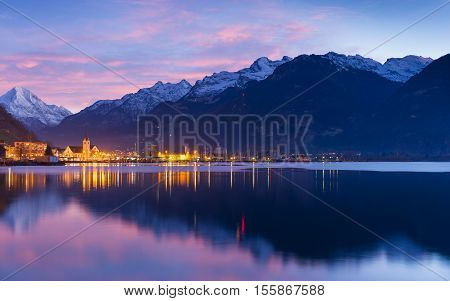 Small town in Swiss Alps. Night sky and clouds sunset painted in red. Lanterns and lights reflected in water of lake.