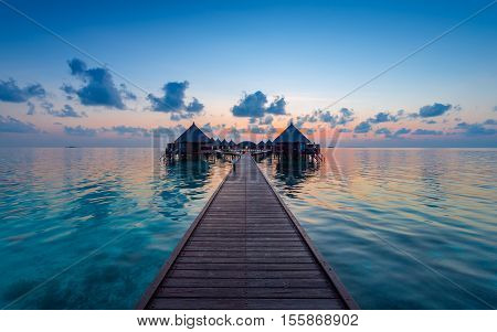 Panorama of tropical island. Turquoise water lagoons coral reefs visible. Sunrise sky and clouds painted in pink. Tourist Resort Deluxe. Maldives