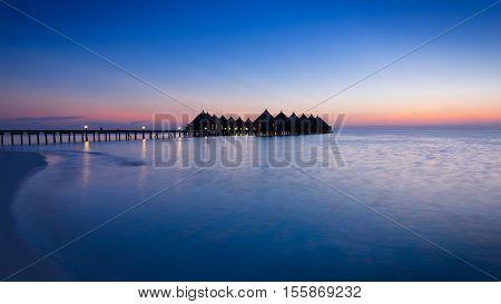 Panorama of tropical island resort with overwater bungalows at night. Maldives. Ari Atoll.