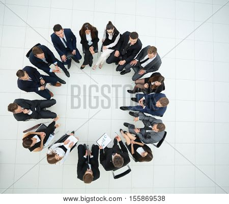 Diverse group pf young business people seated round a table disc