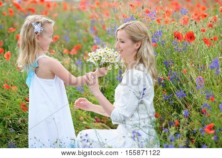 Smiling mother and little daughter on nature in a field of poppies girl is holding flowers. Happy people outdoors