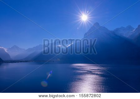 Mountains in the mist blue color. Bright sunrays in a cloudless sky. Lens Flare
