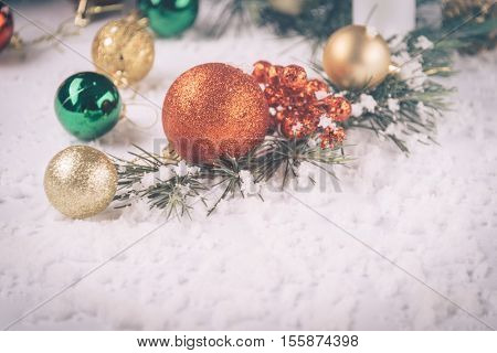 full frame of christmas ornaments on snow.