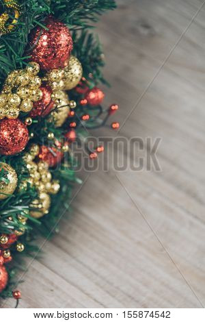 detail of xmas wreath on wood plank.