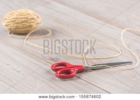 new scissors and a roll of twine, shot from above on light wooden boards background texture, with copyspace; craft concept.