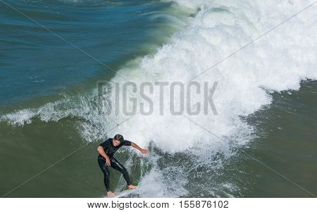 San Diego, USA - September 27, 2013. One surfer on the beach waves. View from the bridge.