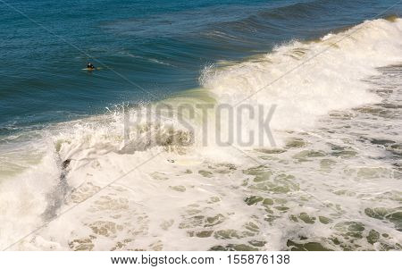 Surfer on the board in waves beach of San Diego California