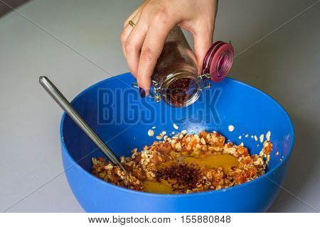 hand pour in red pepper in stuffing from a jar