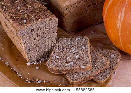 a loaf of bread on the background of cutting boards and other bread and pumpkin