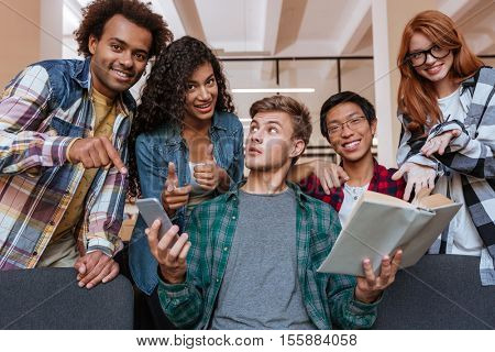 Multiethnic group of cheerful young people standing and pointing on student with book and smartphone