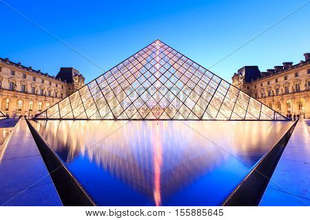 PARIS FRANCE - JULY 19: The Louvre Pyramid at dusk during the Michelangelo Pistoletto Exhibition on July 19 2014 in Paris. The Pyramid is the main entrance to the Louvre Museum.