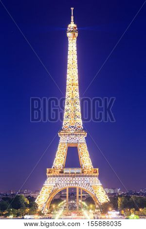 PARIS - JUNE 21: Eiffel Tower brightly illuminated at dusk on JUNE 21 2014 in Paris. The Eiffel tower is the most visited monument of France.