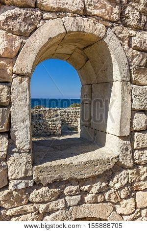 ancient stone wall with a semicircular window and a view of the sea