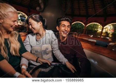 Enthusiastic young people enjoying a ride at amusement park. Young people having fun at amusement park.