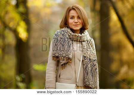 Happy young woman in autumn coat, trendy tippet and beige bag on autumn forest background