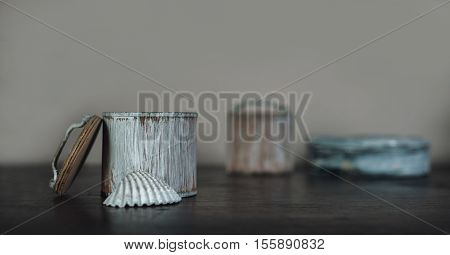 conch and the small boxes painted white on the old brown wooden table