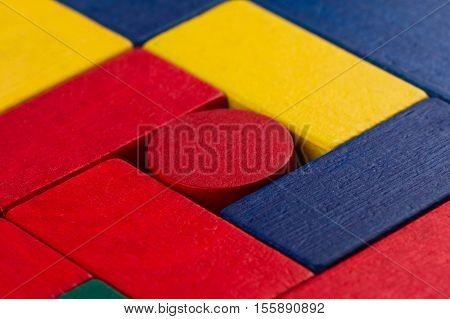 abstract color composition with square wood toy building blocks and a round one in the middle