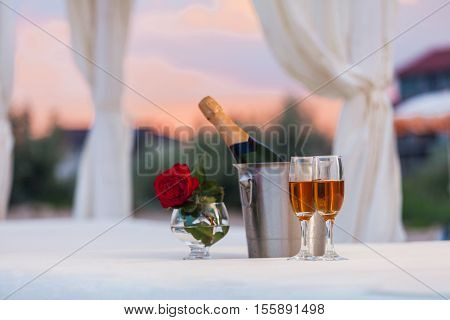 Red Rose, A Bottle Of Wine And Two Filled Glasses