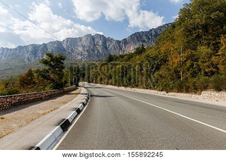 Mountain landscape with asphalt road with fences autumn