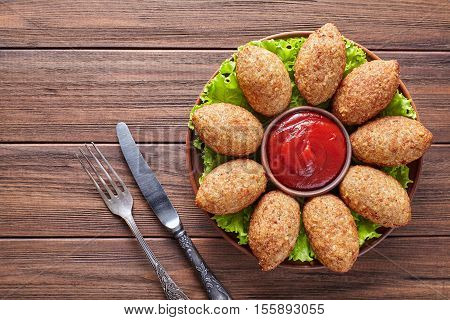 Kibbeh oriental restaurant beef, lamb, goat or camel meat stuffed bulgur kofta spicy meatball fried croquettes on green salad food on rustic wooden table background