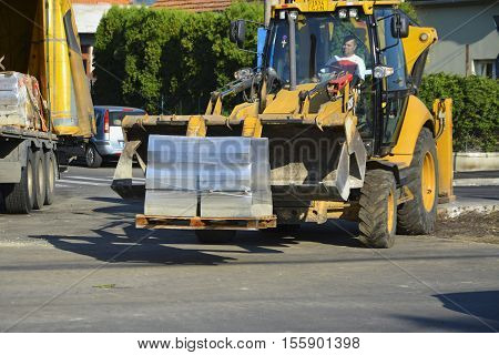CLUJ-NAPOCA ROMANIA - SEPTEMBER 29 2016: Bulldozer with forklift discharges concrete curb blocks on wooden pallet from truck.