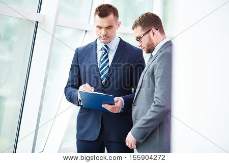 Two businessmen reading a document on clipboard