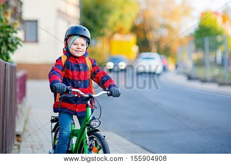 Lovely preschool kid boy in helmet riding with his green bike in the city. Happy child in colorful clothes biking on way to nursery. Active leisure for kids outdoors with bicycle.