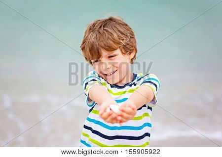 Adorable active little kid boy having fun on Naples beach, Florida. Happy cute child collecting shells.