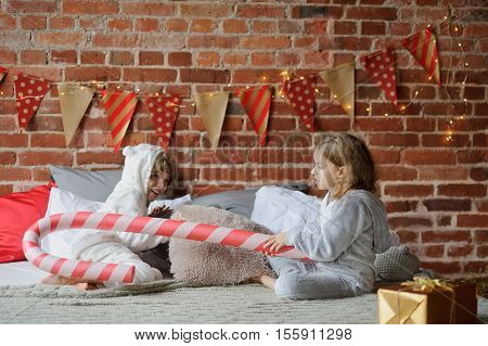 Christmas morning. Two children have put up cheerful fight on a big bed. Brick wall is decorated with Christmas garlands. On the edge of a bed there is a Christmas gift. Children adore Christmas.