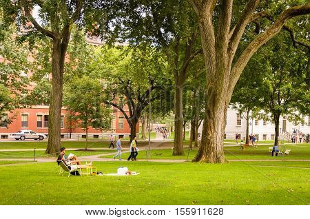 Cambridge, MA, USA - August 19, 2012: Students and tourists rest in lawn chairs and walk around the Harvard Yard, the historic center of the Harvard University campus.
