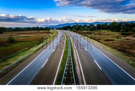 Empty open highway through rural pastoral landscape