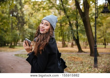 Beauty girl with phone. in warm clothes. stands sideways