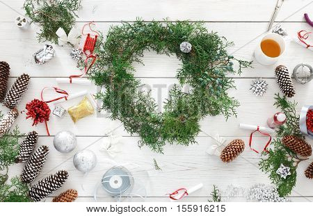 Creative diy craft hobby. Making handmade craft christmas ornaments and thuja tree garland. Home leisure, tools, trinkets and pine cones for holiday decorations. Top view of white wooden table