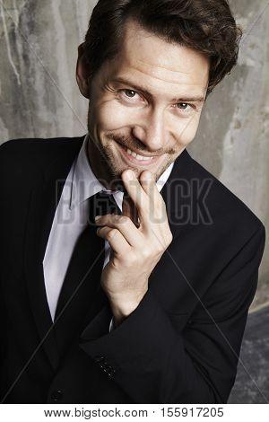 Suave businessman looking at camera studio shot