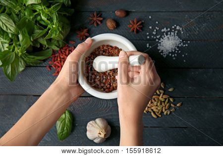 Female hands grinding spices in mortar