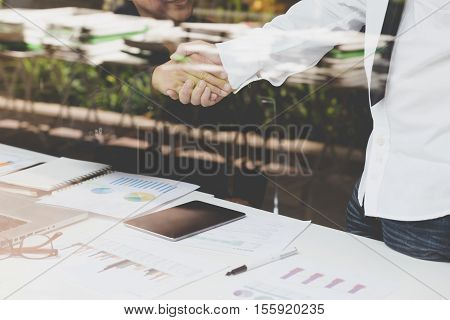 businessman handshaking in office - teamwork cooperation agreement acquisition concept - seen through glass shot