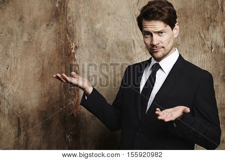 Indifferent handsome businessman looking at camera studio