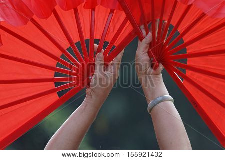 HANOI VIETNAM Octobre 23 2016 : The hands of a fan dancer liven up two red fans during a traditional Vietnamese dance.