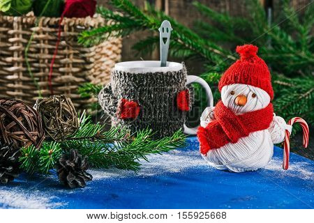 Handmade yarn snowman holding candy cane on the background of christmas decorations and mug of hot drink